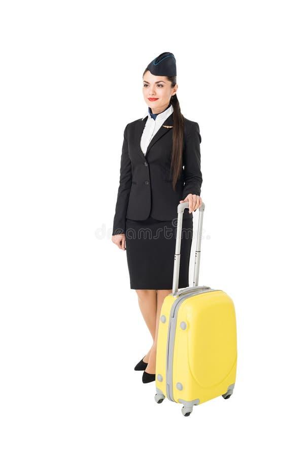 Молодой женский stewardess полагаясь на чемодане стоковые фотографии rf