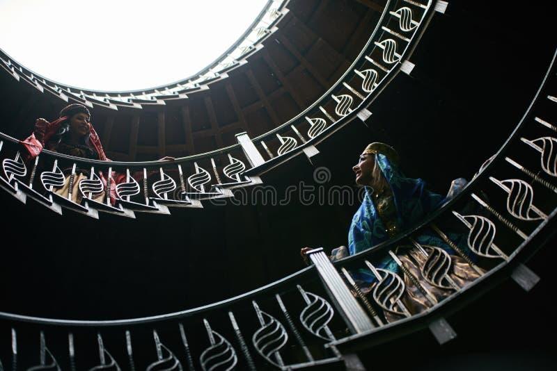 2 молодой женщины стоя на спиральной лестнице и имея потеху стоковые фото