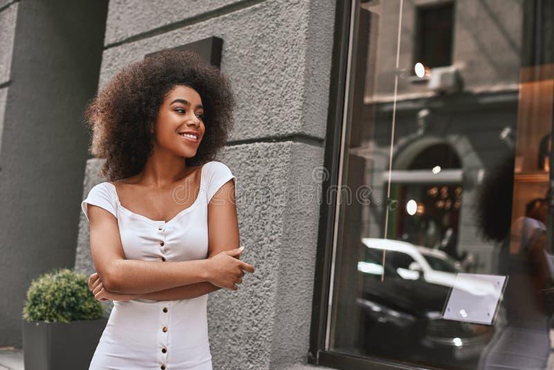 Молодой и полный энергии Портрет женщины шикарного Афро американской стоя outdoors с пересеченными оружиями и усмехаться стоковое фото rf