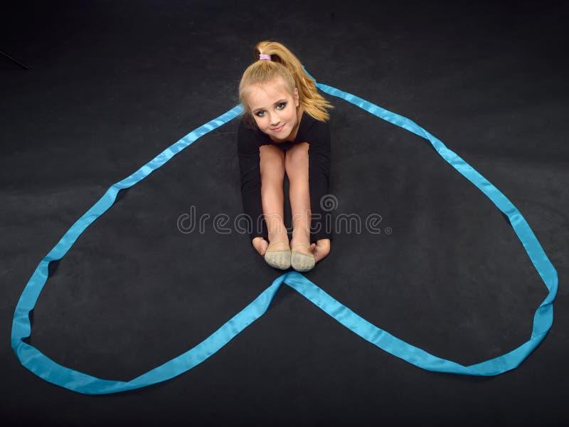 Молодой красивый белый кавказский гимнаст девушки отдыхая на поле с голубой лентой Гимнастическая лента в форме сердца стоковое фото rf