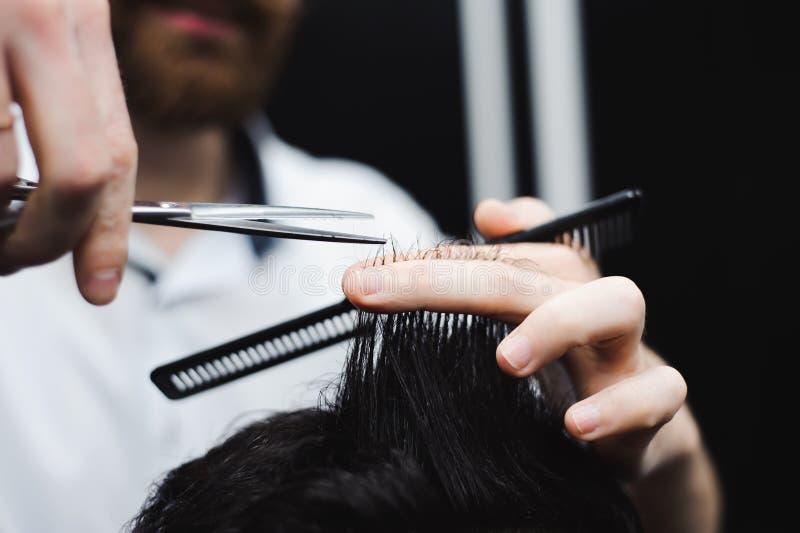 Молодой красивый парикмахер делая стрижку привлекательного человека в парикмахерскае стоковое фото