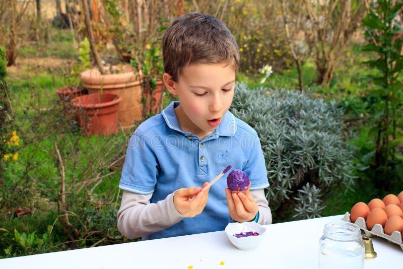 Молодой мальчик крася пасхальные яйца на открытом воздухе во Франции Деятельность при детей пасхи творческая стоковая фотография
