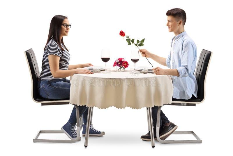 Молодой мужчина давая розу молодой женщине на таблице ресторана стоковые изображения