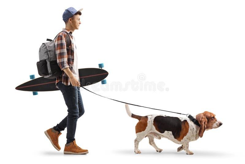 Молодой парень с рюкзаком и longboard идя гончая собака выхода пластов стоковое фото rf