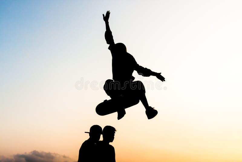 Молодой скейтбордист пробуя поскакать 2 мальчика со скейтбордом стоковая фотография