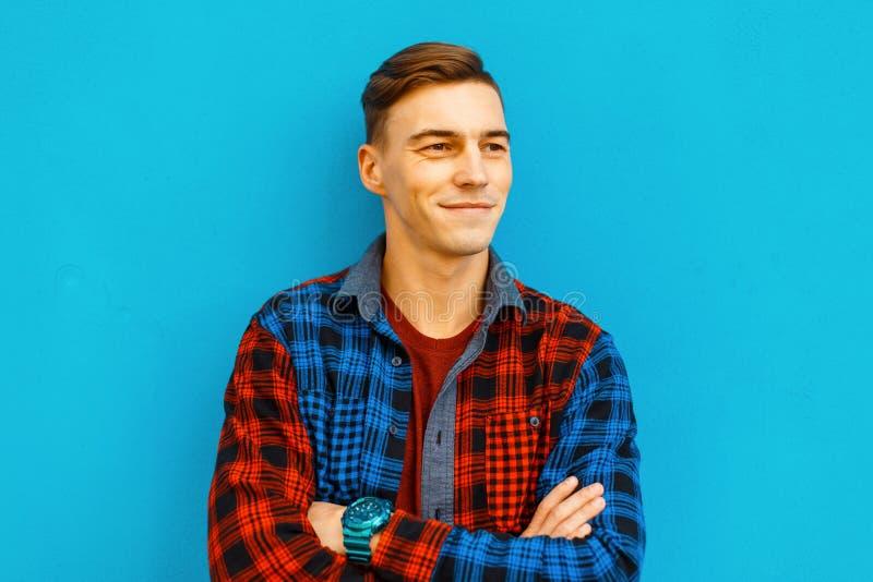 Молодой смешной жизнерадостный человек со стильным стилем причесок с милой улыбкой в модной футболке в винтажной checkered красоч стоковые фотографии rf