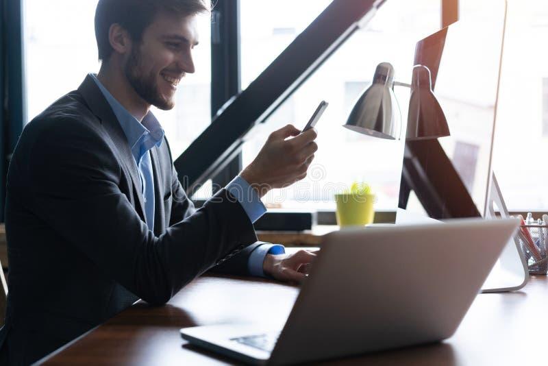 Молодой счастливый бизнесмен усмехаясь пока читающ его smartphone Портрет усмехаясь сообщения чтения бизнесмена с стоковые фото