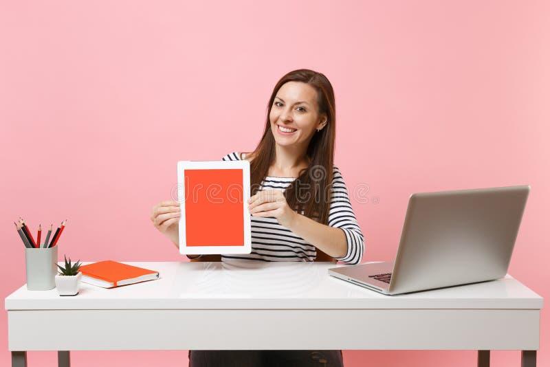 Молодой усмехаясь планшет владением женщины с пустым пустым экраном сидеть работа на белом столе с современным ноутбуком ПК стоковое фото rf