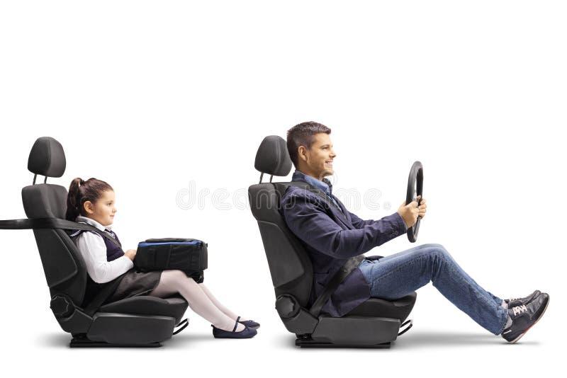 Молодой человек в автокресле с прикрепленным ремнем безопасности держа streering колесо и его дочь за им стоковая фотография