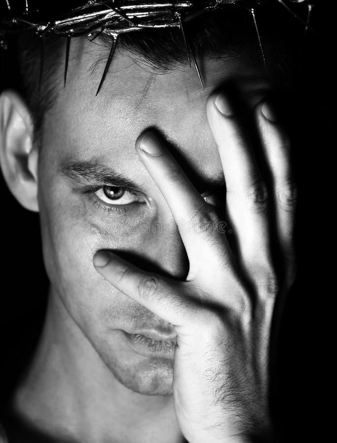 Молодой человек в кроне терниев, мученик покрывает его сторону с сожалениями руки стоковые фото