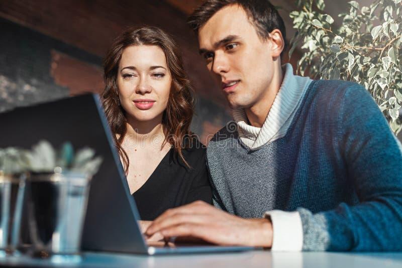 Молодой человек и женщина работая перед ноутбуком Встреча команды, процесс работы стоковое фото