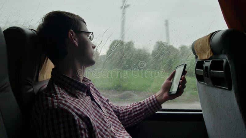 Молодой человек проверяя электронные почты на его коммутирует к работе шиной в длинном отключении Конец-вверх использования мобил стоковое фото