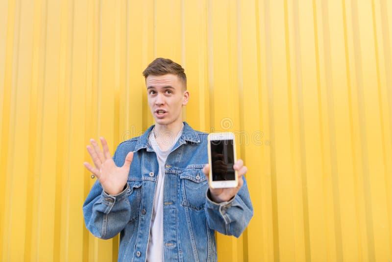 молодой человек стоит со смартфоном в его руках на фоне желтой стены Фокус на человеке стоковые фотографии rf