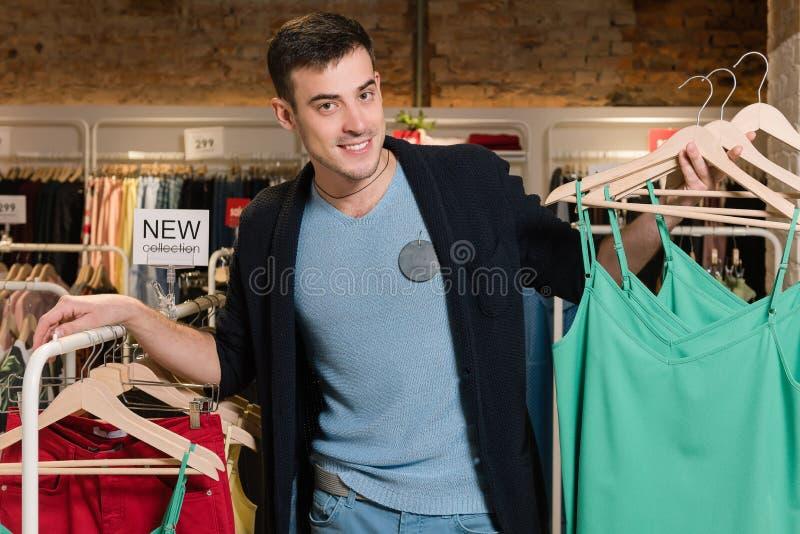 Молодой человек с одеждами на вешалках в магазине стоковые изображения rf