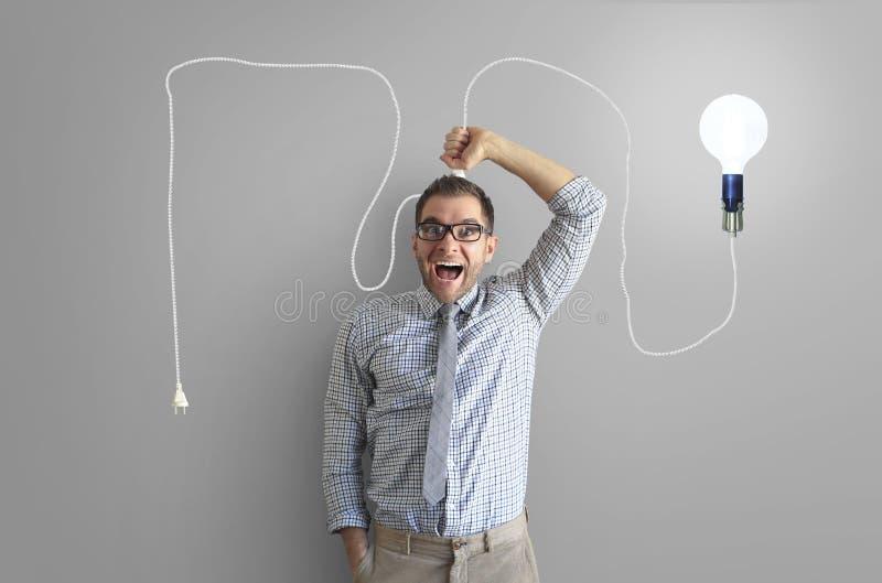 Молодой человек усмехается и держится яркую электрическую лампочку стоковое фото rf