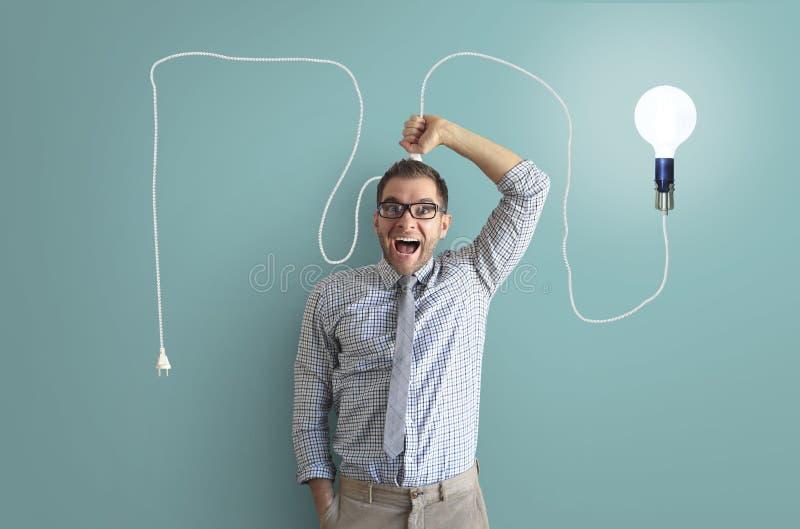 Молодой человек усмехается и держится яркую электрическую лампочку стоковые фото