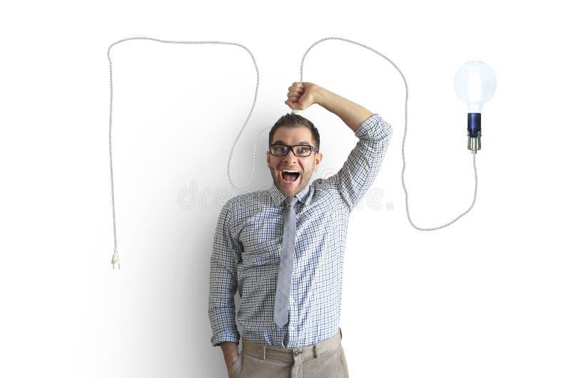Молодой человек усмехается и держится яркую электрическую лампочку стоковое фото