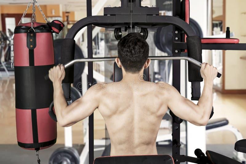 Молодой человек тренирует его мышечные оружия на спортзале стоковая фотография rf