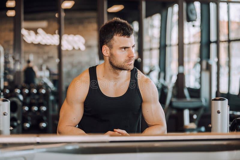 Молодой человек отдыхая в здоровом спортзале клуба после работать стоковое изображение