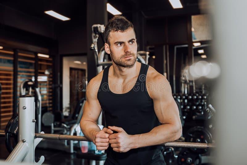 Молодой человек отдыхая в спортзале после работать стоковая фотография