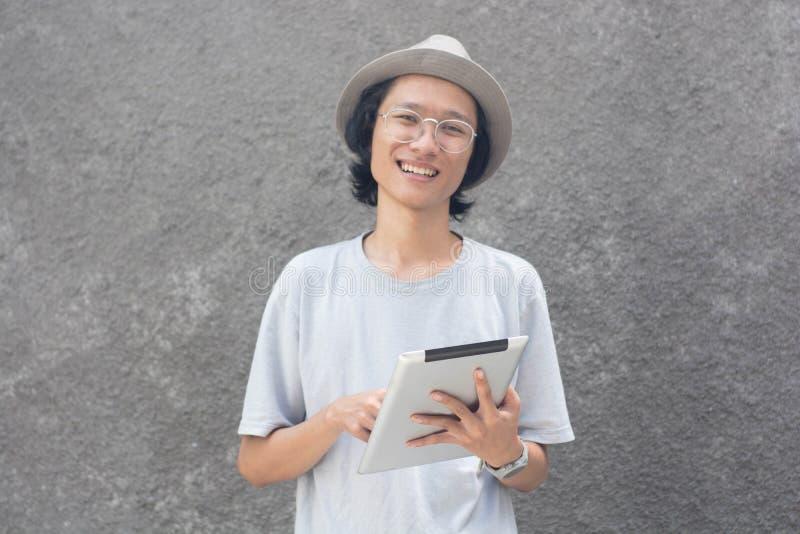 Молодой atractive творческий азиатский человек со шляпой и стеклами используя планшет и усмехаться fedora на камере стоковая фотография