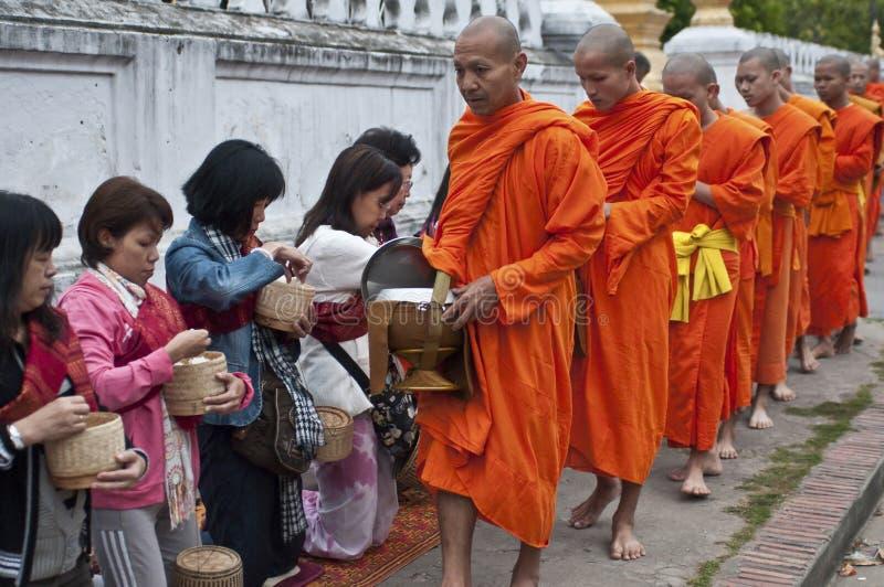 Монахи собирая милостыни от людей, Luang Prabang, Лаоса стоковые фото