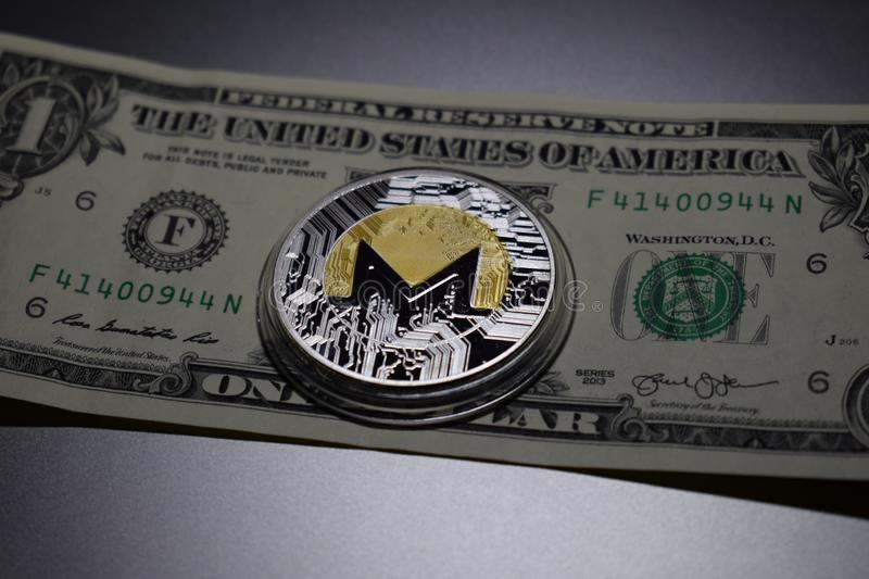 Монетка cryptocurrency Monero на одной банкноте доллара стоковое фото