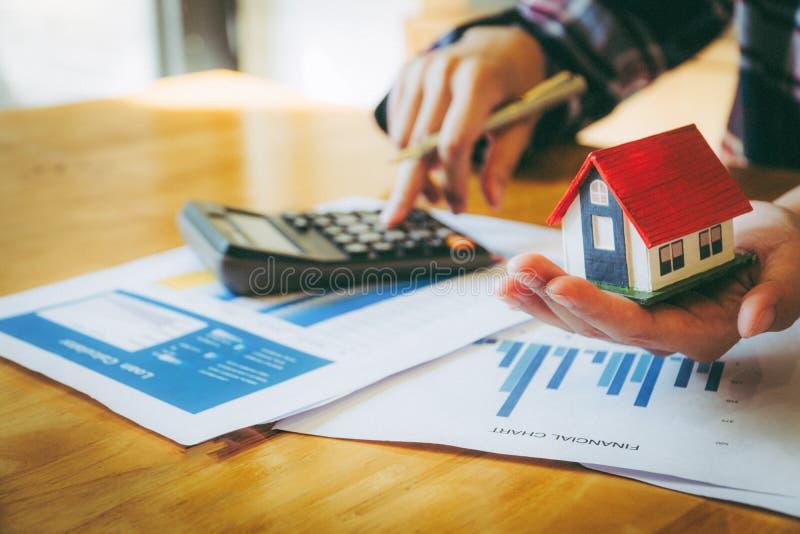 Модель дома удерживания женщины в руке и высчитывать финансовую диаграмму для вклада к покупая свойству стоковое изображение rf