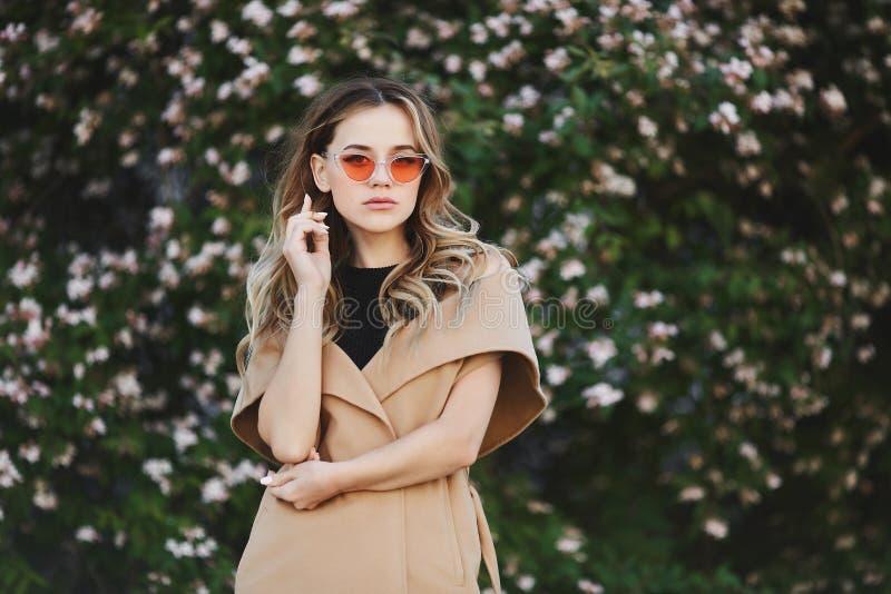 Модная и чувственная белокурая модельная девушка в безрукавном пальто и в стильных солнечных очках стоковое фото rf