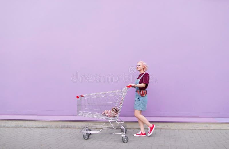 Модная маленькая девочка с корзинами идя вниз по улице на предпосылку пурпурной стены стоковые фото