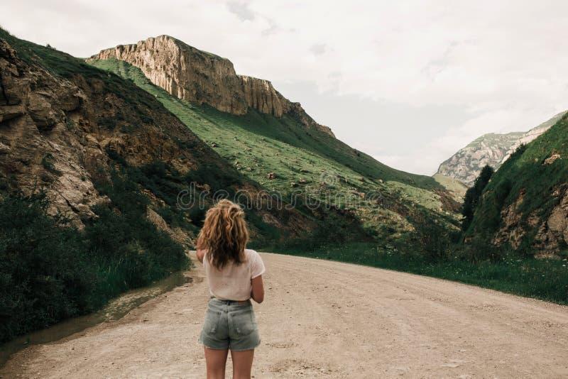 Модная девушка в белых одеждах стоя на дороге в гористых местностях Зеленая трава и горы стоковые фотографии rf