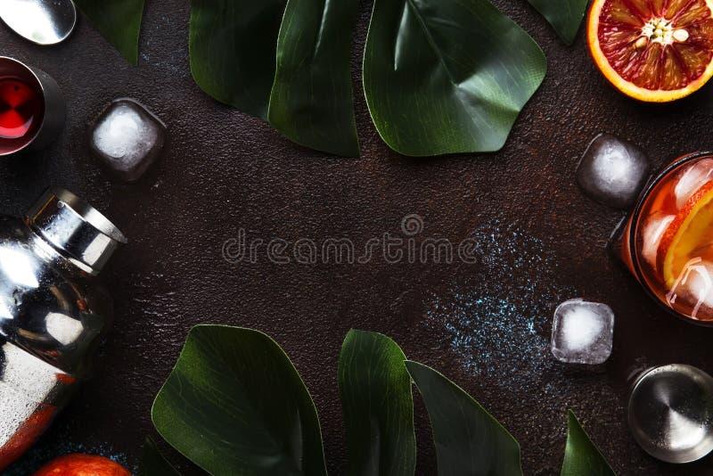 Модный спиртной коктейль Negroni с сухим джином, красным вермутом и красными кубами горьких, апельсина и льда Счетчик бара Брауна стоковые изображения rf