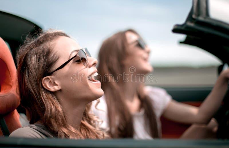 2 модных девушки путешествуют в обратимом автомобиле стоковая фотография