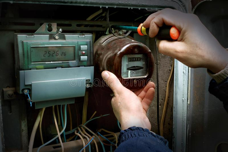 The electrician dismantles the old analog electricity meter royalty free stock images