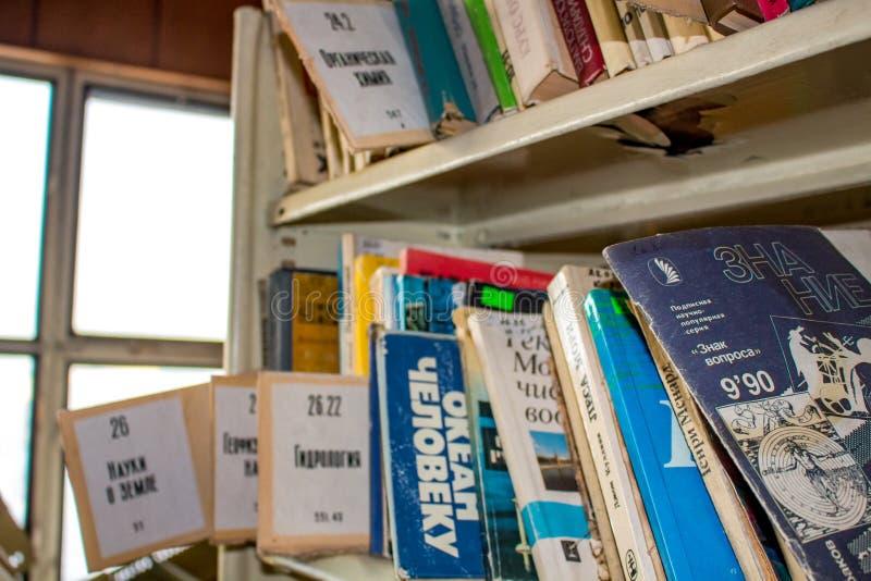 Москва, Россия - январь 2015: Получившаяся отказ библиотека фабрики, старые советские книги на полках стоковое фото