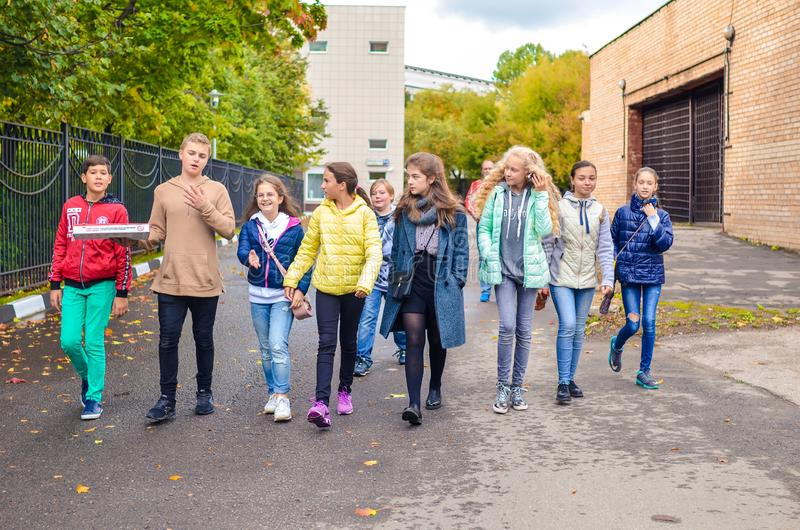 Москва, Россия, 23-ье сентября 2018 Группа в составе молодые мальчики и девушки говоря и идя вниз с дороги стоковое изображение rf