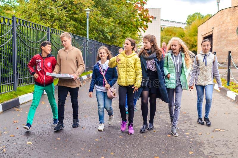 Москва, Россия, 23-ье сентября 2018 Группа в составе молодые мальчики и девушки говоря и идя вниз с дороги стоковые фото