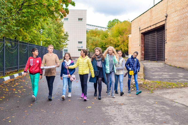 Москва, Россия, 23-ье сентября 2018 Группа в составе молодые мальчики и девушки говоря и идя вниз с дороги стоковые фотографии rf