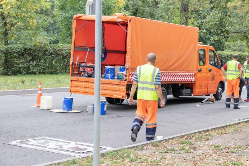 МОСКВА, РОССИЯ - 9-ОЕ СЕНТЯБРЯ 2018: Работники ремонта дорог, roadmen ремонтируя асфальт в городе летом стоковое фото rf