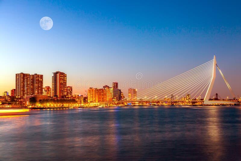Мост Erasmus над рекой Мёзом с небоскребами и луна в Роттердаме, южной Голландии, Нидерланд во время захода солнца сумерек стоковые изображения rf