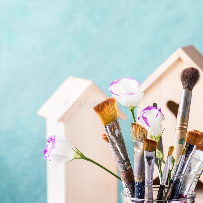 Набор щетки искусства и деревянный дом для украшения на предпосылке бирюзы стоковое изображение rf