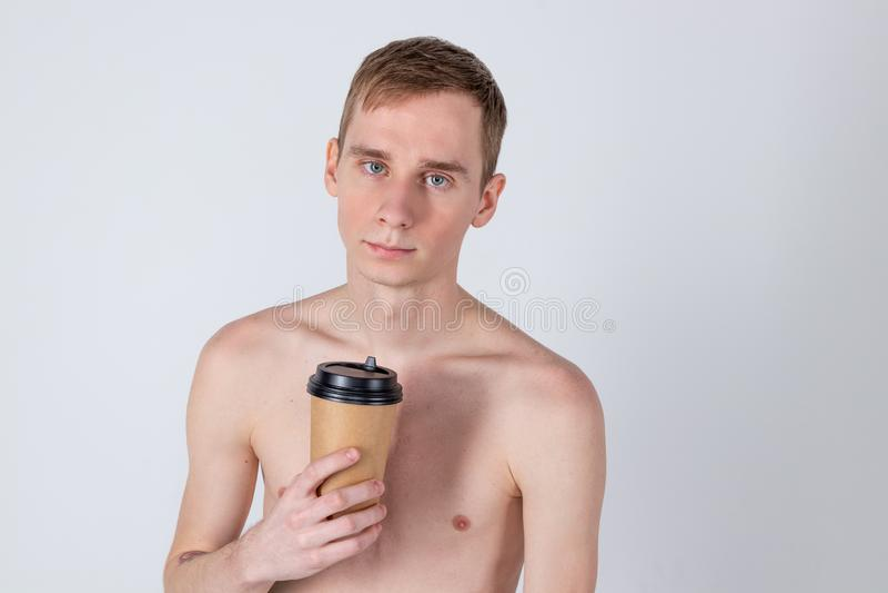 Нагой красивый напиток парня от чашки кофе или чая Освежение и напиток утра стоковая фотография