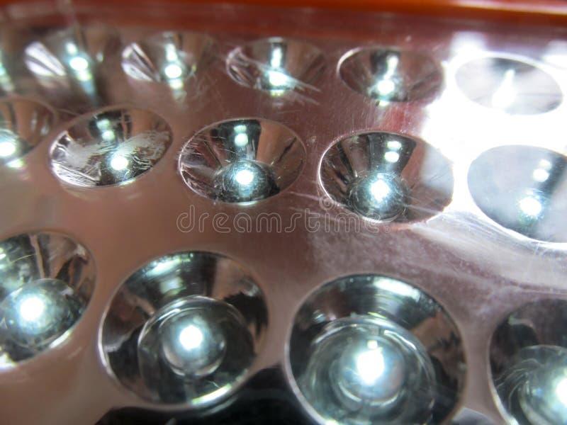 Накаляя шарики диода и поцарапанная поверхность зеркала электрофонаря стоковые фото