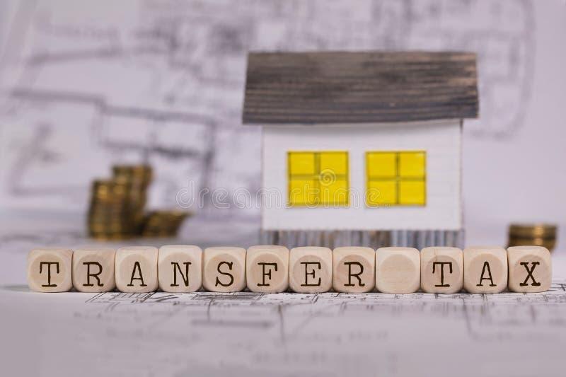 НАЛОГ НА ПРОДАЖУ ЦЕННЫХ БУМАГ слов составленный деревянных писем Малый бумажный дом на заднем плане стоковые фотографии rf