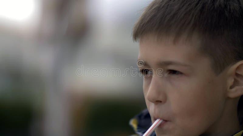 Напитки мальчика milkshake на кафе outdoors стоковое фото