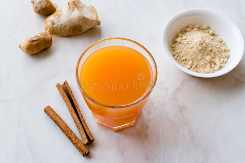 Напиток Jamu здоровый азиатский с ручкой турмерина и циннамона, апельсиновым соком стоковое фото rf