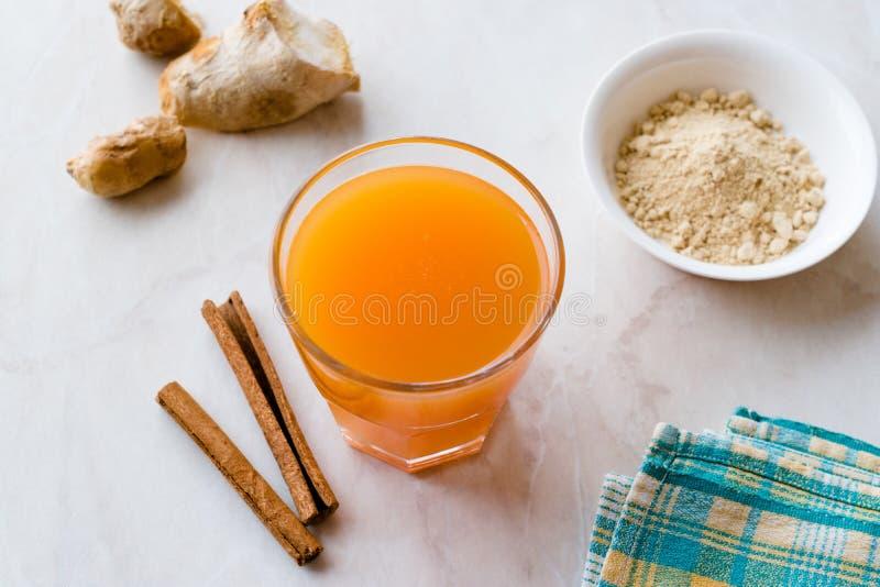 Напиток Jamu здоровый азиатский с ручкой турмерина и циннамона, апельсиновым соком стоковое изображение rf