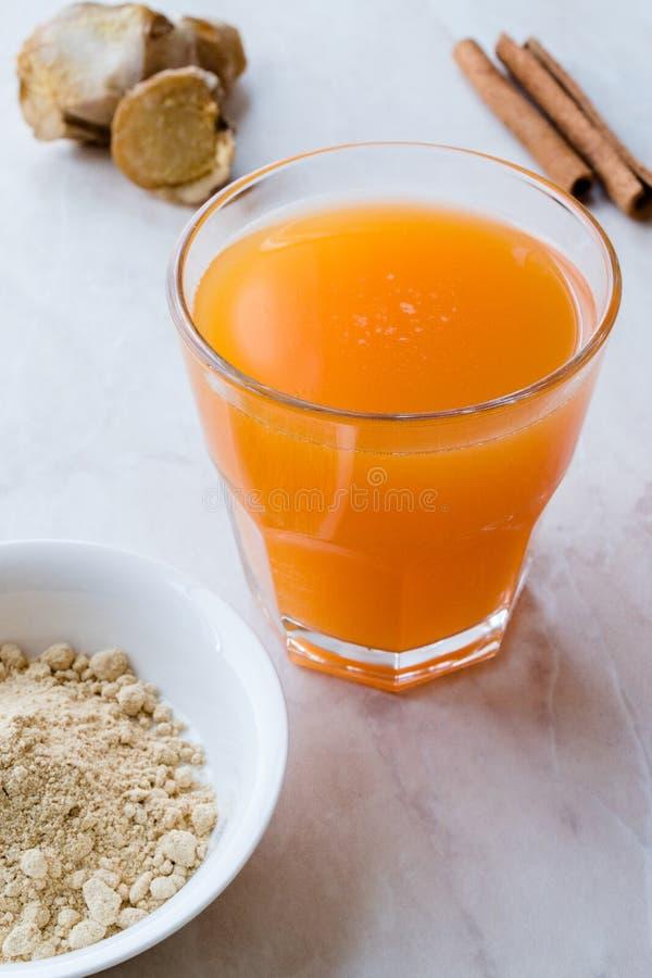 Напиток Jamu здоровый азиатский с ручкой турмерина и циннамона, апельсиновым соком стоковые фото