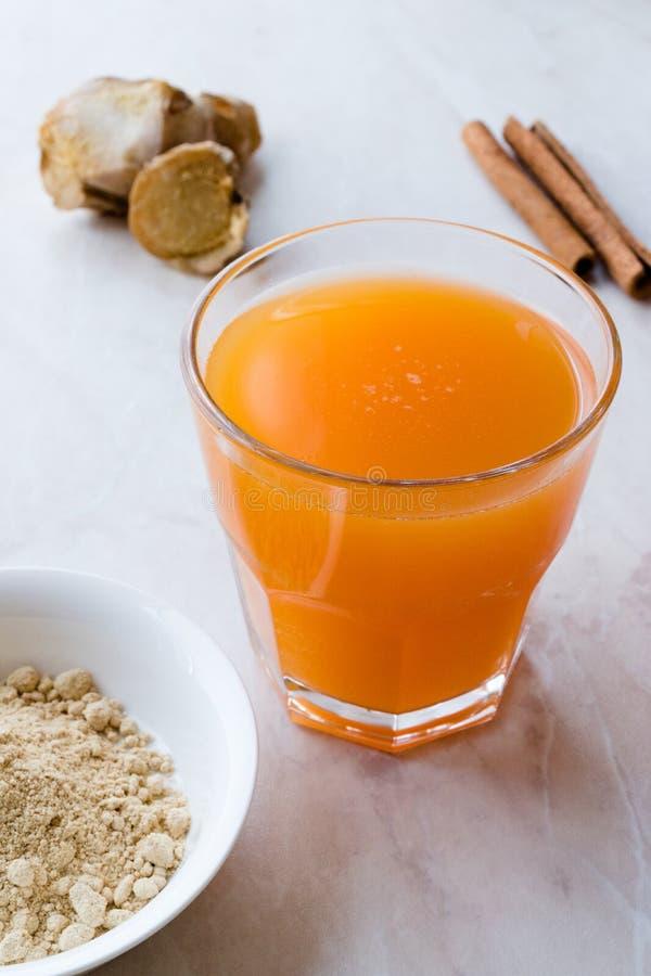 Напиток Jamu здоровый азиатский с ручкой турмерина и циннамона, апельсиновым соком стоковое фото
