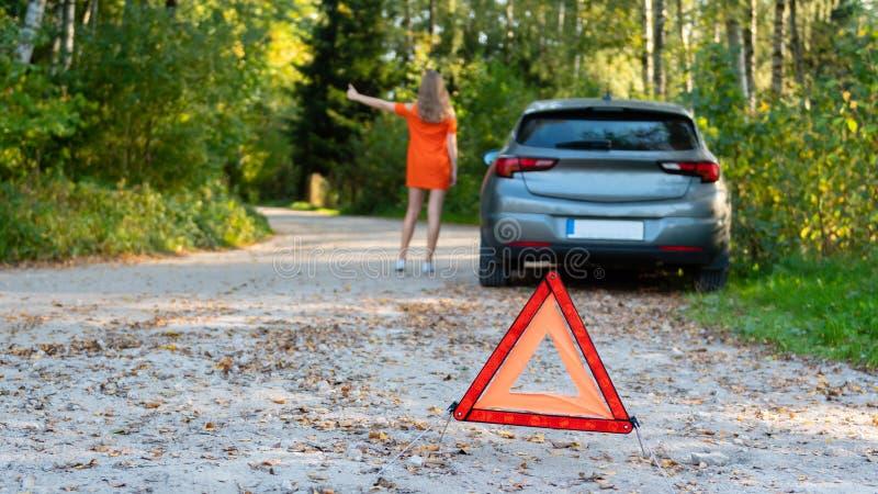 Напряженный водитель молодой женщины путешествует автостопом и останавливает автомобили, просит помощь как имеет проблему с brock стоковое фото rf